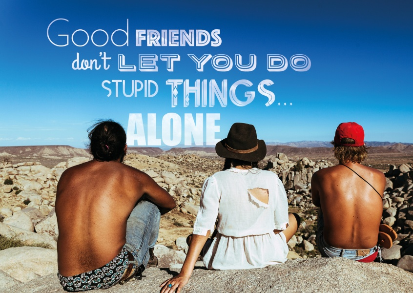 Drei freunde sitzen auf felsen mit blick in die ferne und darüber steht  good friends don`t let you do stupid things alone.